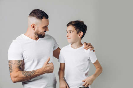 Father shows thumbs up to his kid, isolated on grey background. daddy cheers his son up. well done. atta boy, goo of you, excellent. man is proud of his little brother.