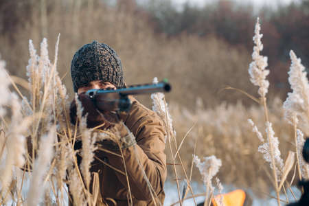 close up photo. young bearded man is going to use his rifle. copy space. sharpshooter Stock Photo