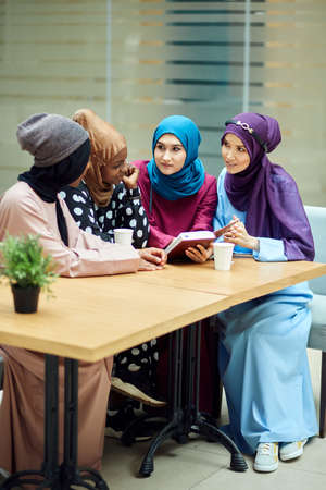 Muslim young women of diverse ethnicity, dressed in colourful national clothes chilling at cafe, talking about new book of famous author