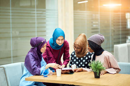 Photo of a happy young multiethnic arabian business women dressed in hijab reading book in modern cafe.