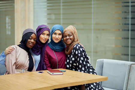 Portrait of smart elegantly dressed caucasian and african muslim female friends look at camera with cheerful expression at office background