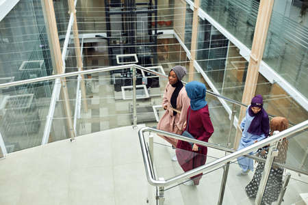 Young muslim cheerful business traveller women in national arabian clothings visiting business centre, coming up the stairs chatting about their future plans of sightseeing of Dubai