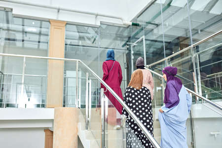 Group of smiling muslim women in hijab walking up the stairs of business centre. Arabian and african ladies dressed in long smart dresses and scarfs going to conference hall