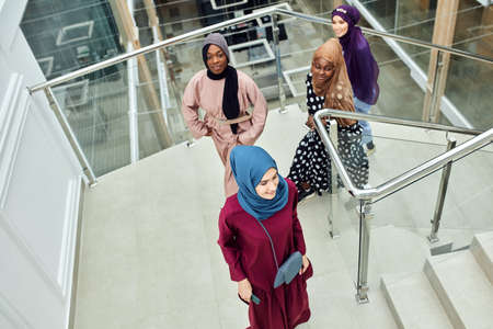 Multicultural group of female Arabian students, dressed in national dresses and scarfs climbing the stairs of university , sharing ideas with each other on the way
