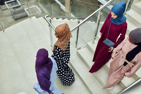 Group of smiling muslim women in hijab walking down the stairs of business centre. Arabian and african ladies dressed in long smart dresses and scarfs going to conference hall 스톡 콘텐츠