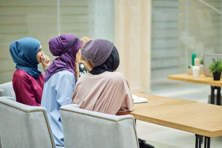 Rear view of multiracial group of muslim women dressed in smart national clothes studying at college. Education, Social diversity, friendship. 스톡 콘텐츠