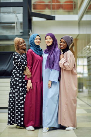 Diverse muslim multiethnic female representatives participating in international conference, posing in lobby of business centre
