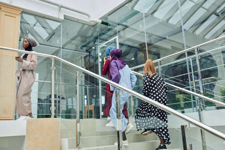 Multiracial group of muslim business women visiting international conference at business centre, walking up the staircase sharing impressions and ideas after event
