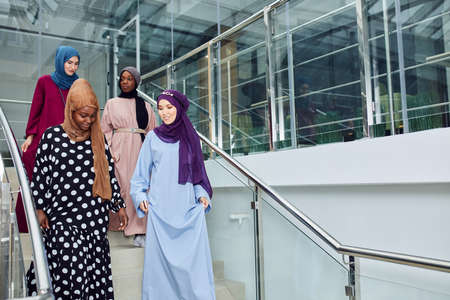 Multicultural group of female Arabian students, dressed in national dresses and scarfs going down the stairs of university, sharing ideas with each other on the way 스톡 콘텐츠