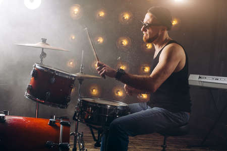 gorgeous man in jeans and T-shirt making music with drums set. side view photo Imagens
