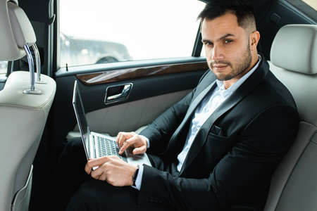 Caucasian man wearing formal wear sit with laptop in expensive luxurious car, side view 免版税图像