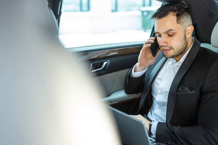 Handsome bearded man working on laptop while talking on phone in his luxurious car, side view