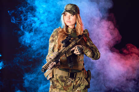 Female soldier in military camouflage uniform and cap holding sniper rifle over black background with smoky clouds