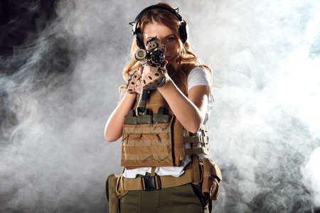 Airsoft female shooter playing strikeball, sets her sights on enemy with automatic assault rifle. Studio shot, dark smoky background.