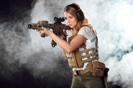 Portrait of a beautiful woman warrior in military outfit with firearm in hands, aiming at enemy, fighting in smoke from exploding shells at night Banco de Imagens