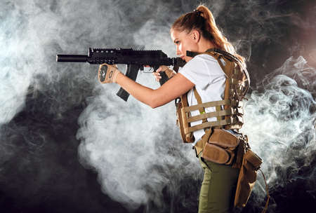 Calm concentrated woman marksman in sniper gear holding rifle in hand aiming at enemy s head in dark smoky background Banco de Imagens