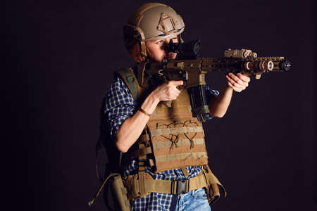 Female civil in tactical uniform with rifle. Shot in studio on black background. Casual woman citizen forced to defend herself