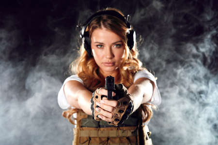 Armed beautiful blonde woman wearing protective headphones and plate carrier, shoots with gun at a target in the darkness with smoke clouds 免版税图像