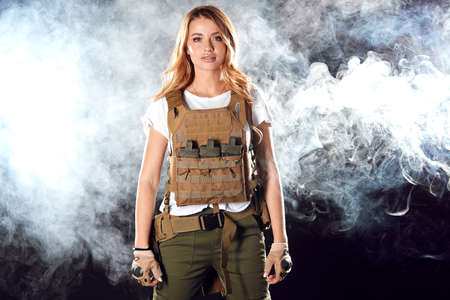 Gorgeous young woman with long blonde hair wearing Military gear, posing isolated in studio against dark wall with smoke on background