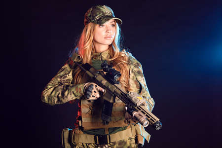 Sniper woman in ghillie suit, cap and plate carrier holds airsoft rifle over black background