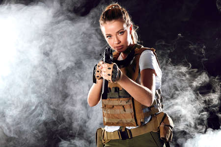 woman sniper in body armour with SVD sniper rifle. Female serving in Army, soldier with machine gun. Shot in studio. Smoky dark background imitating explosions
