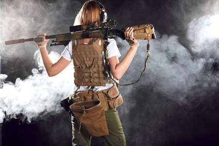woman sniper with SVD sniper rifle. Female in Army, soldier with rifle. Military training, weapons. Shot in studio.