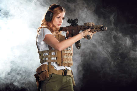 woman sniper with SVD sniper rifle. Female in US Army soldier with rifle. Shot in studio. Banco de Imagens