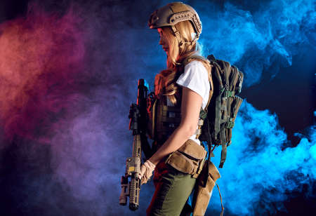 Heavily armed and well-equipped female soldier in battle helmet holding assault rifle isolated on dark smoky battlefield. Paint ball and laser tag sport games 스톡 콘텐츠