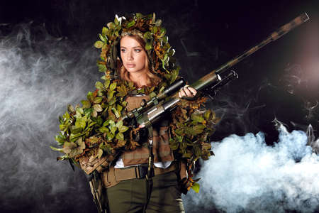 Heavily armed female soldier in battle helmet and ghillie suit holding assault rifle isolated on dark smoky battlefield. Paint ball and laser tag sport games