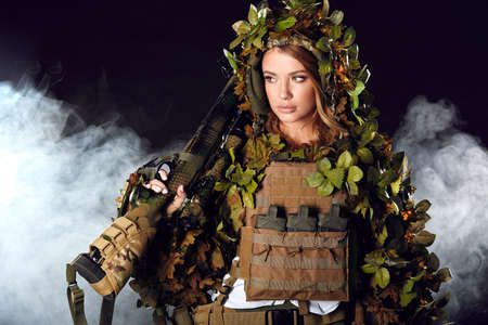 Heavily armed and well-equipped female soldier in battle helmet holding assault rifle isolated on dark smoky battlefield. Paint ball and laser tag sport games Banco de Imagens