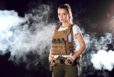 Portrait beautiful blonde female soldier dressed in plate carrier and warbelt. Women, army, weapon, technology and people concept. Black smoky background.