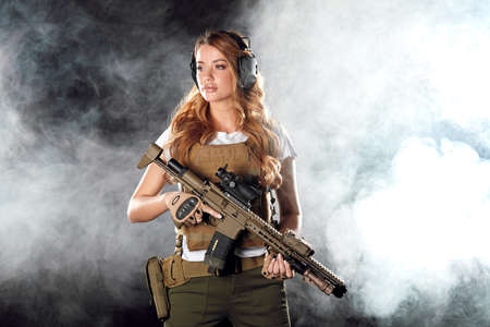 Woman in the army pros and cons. Women do not just serve, but attain high positions and ranks. Beautiful woman in military outfitholding weapon in hands stands in smoky background