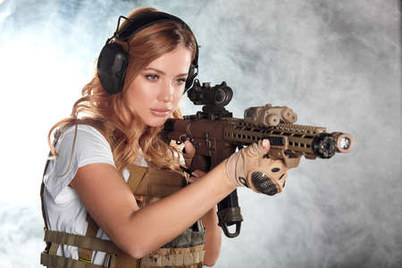 Girl marksman in sniper gear holding sniper rifle in hand aiming at enemy s head in dark smoky background