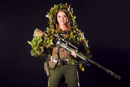 Woman soldier sniper in disguise poses with a sniper rifle and aims in the smoky darkness