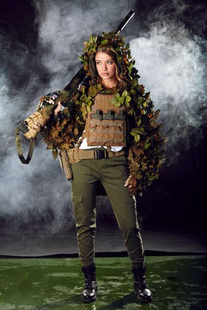 Camouflaged woman sniper in ghillie suit posing with rifle in foggy night. Special Weapons and Woman Concept. Banco de Imagens