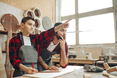 family, carpentry, woodwork and people concept - Male kid pointing with finger at something and craftsman looks at it at workshop