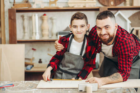 Dad and son dressed in work uniform and aprons consulting with drawings posted on the internet using smartphone, while making wooden toy airplane. Carpentry and joinery class concept