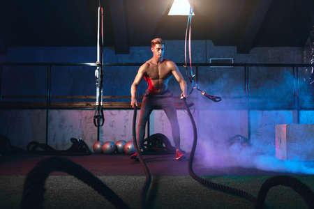Functional training, Healthy lifestyle and Strong well trained body. Muscular powerful man training with rope in functional training gym Standard-Bild