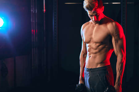 Young caucasian male trainer with muscular well-trained torso posing at cross fit studio holding dumbbells in hands Standard-Bild