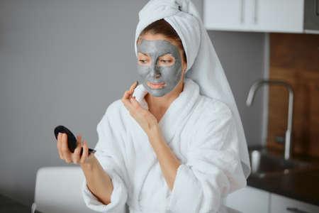 young caucasian woman applying facial mask wearing bathrobe and towel in bedroom, look at camera