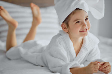 awesome cute little girl of caucasian appearance wearing bathrobe and towel, lies on bed
