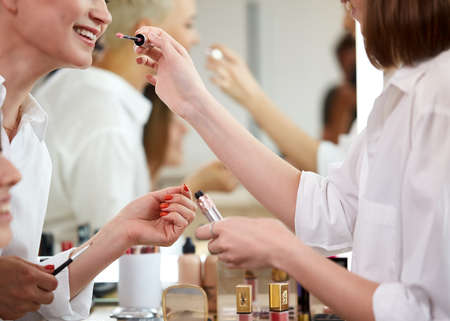 side view on make-up artist going to apply lipstick on smiling girl, doing make-up in beauty studio
