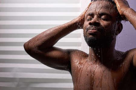 good looking man wet taking shower in bath