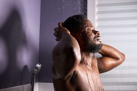 young african man with bare torso in bathroom, takes shower. morning routine. fresh at morning. hygiene at morning concept 版權商用圖片