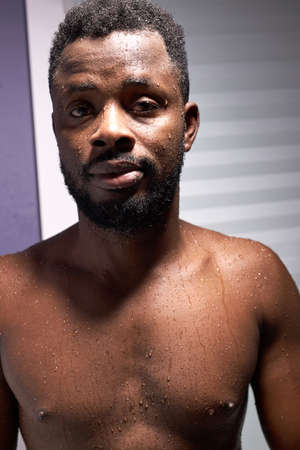 portrait of black african after shower, young bearded dark skinned guy look at camera Stockfoto
