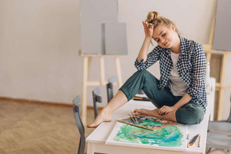 awesome smiling pretty woman in checked shirt and pants having a rest while painting in the art class. full length photo. free time. copy space