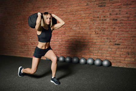 Young female athlete doing lunges with weight, holding in hands heavy sandbag during circuit functional training at cross fit studio Stock Photo