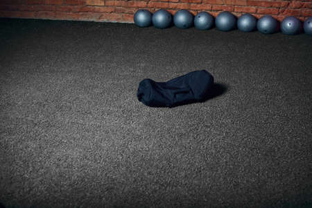 Cross fit equipment for weight work-out . Dark sandbag lying isolated on grey floor in gym Stock Photo
