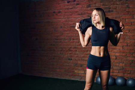 Caucasian athletic woman with well-trained body, dressed in black sportswear with shorts posing with sandbag while exercises in the gym. Reklamní fotografie