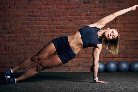 Young woman with well-trained body keeping side plank pose while exercising in the gym